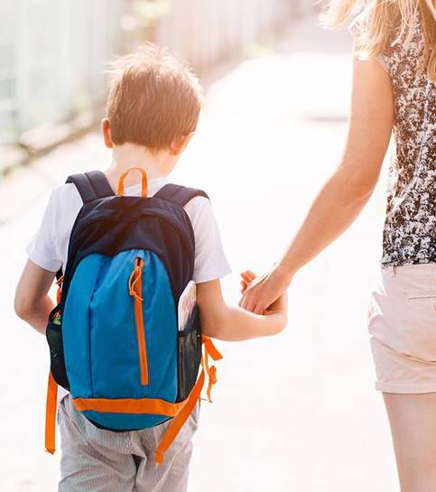 Niño de 7 años que va a la escuela con su madre