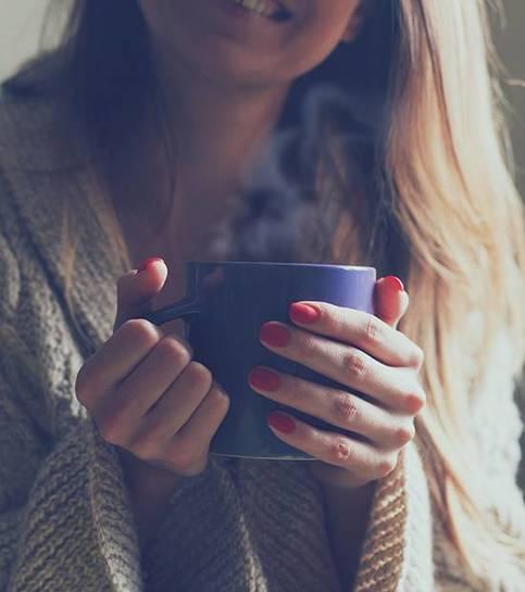 Trzymając filiżankę gorącej kawy