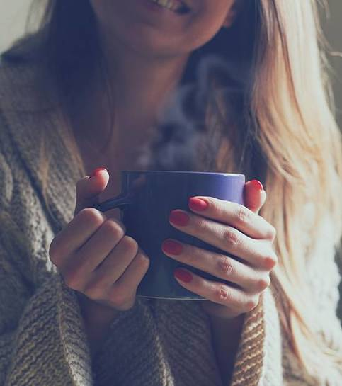 Držící šálek horké kávy