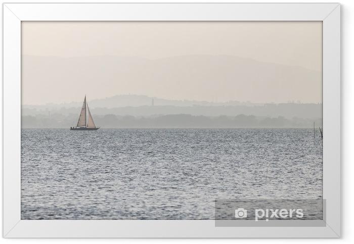 Plakat w ramie Mała żaglówka nad jeziorem, z odległymi wzgórzami w tle i bardzo miękkie kolory, głównie białe i jasnoniebieskie - Styl życia