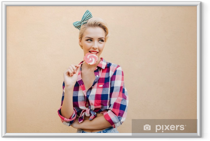 Poster in Cornice Happy cute pin up ragazza in piedi e mangiare lecca-lecca colorati - Persone