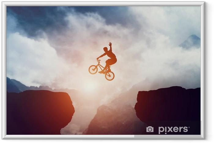 Plakát v rámu Muž skákat na bmx kolo přes sráz v horách při západu slunce. - Sport