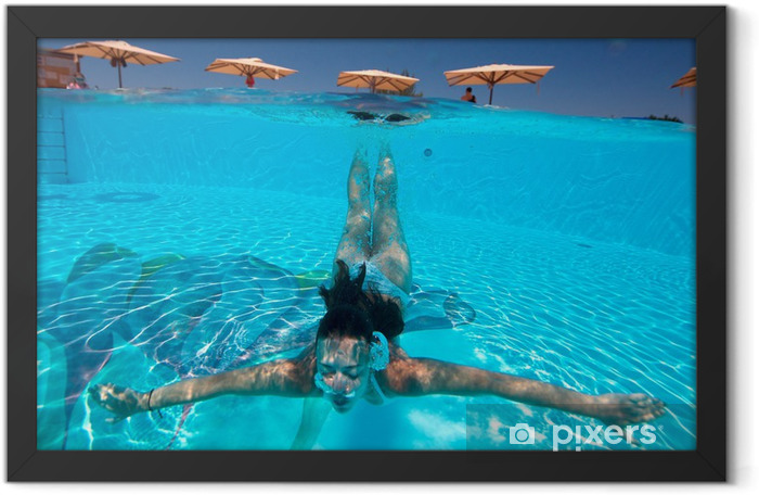 Underwater view of a woman swimming in the swimming pool Framed Poster - Water Sports