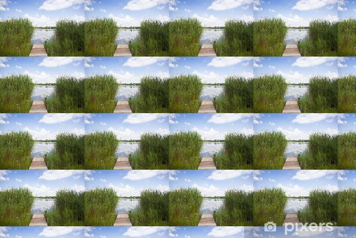 Papier peint vinyle sur mesure Passerelle en bois menant au lac à travers les hautes herbes - Eau