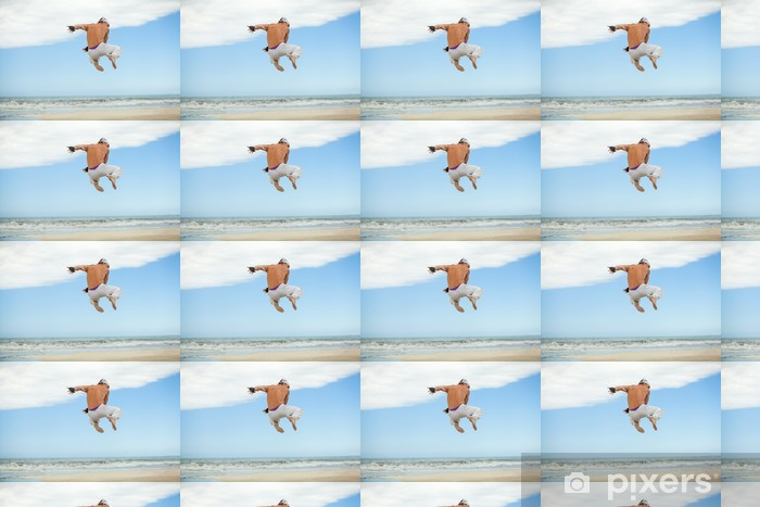 Papier peint vinyle sur mesure Erwachsener sportlicher Mann am Strand springt karaté - Art martial