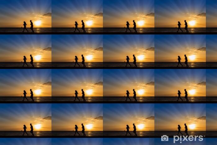 Tapeta na wymiar winylowa Sylwetki ludzi jogging na plaży z zachodem słońca backgroun - Tematy