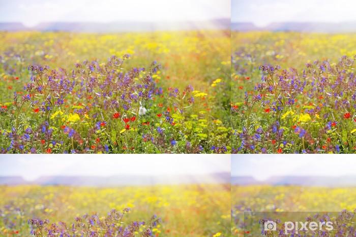 Vinyltapet Fält med gräs, violetta blommor och rött. - Frihet