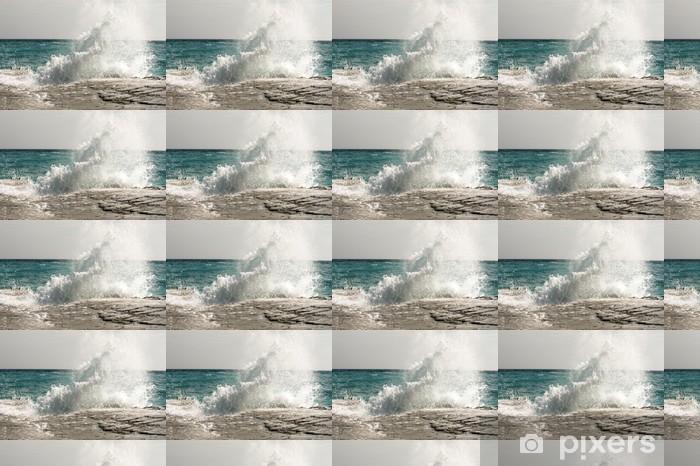 Vinyltapete nach Maß Die Wellen auf einem steinigen Strand brechen, wodurch ein Spray - Wasser