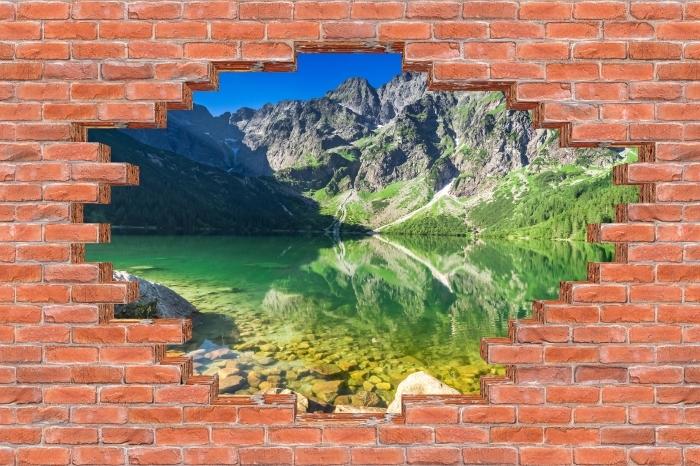 Fototapeta winylowa Dziura w murze - Jezioro w górach - Dziury w ścianie