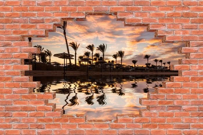 Fototapeta winylowa Dziura w murze - Zachód słońca nad piaszczystą plażą i palmami. Egipt. - Dziury w ścianie