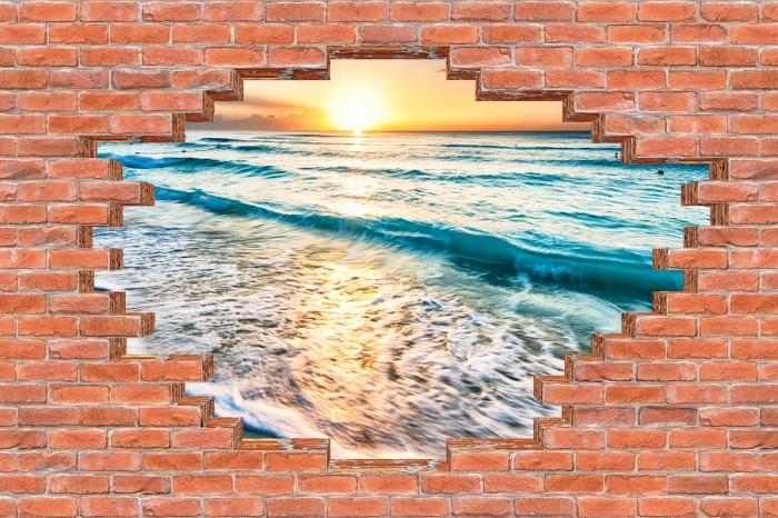 Fototapeta winylowa Dziura w murze - Wschód słońca na plaży - Dziury w ścianie