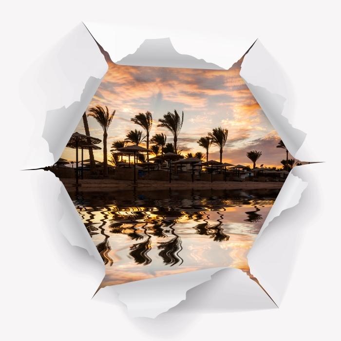 Fototapeta winylowa Dziura w ścianie - Zachód słońca nad piaszczystą plażą i palmami. Egipt. - Dziury w ścianie
