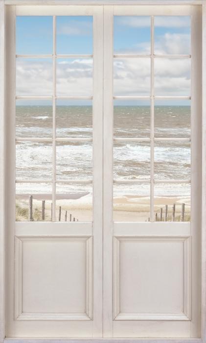Fototapeta winylowa Białe drzwi - Piasek na plaży w słoneczny dzień - Widok przez drzwi