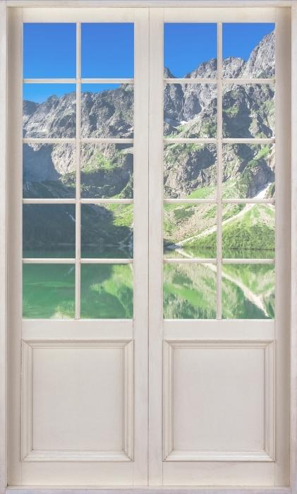 Vinyl-Fototapete Weiße Tür - See in den Bergen - Blick durch die Tür