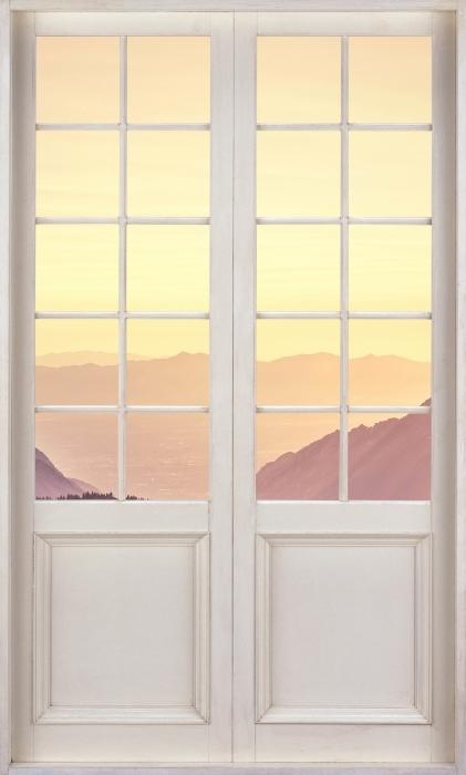 Fototapeta winylowa Białe drzwi - Zachód słońca w górach - Widok przez drzwi