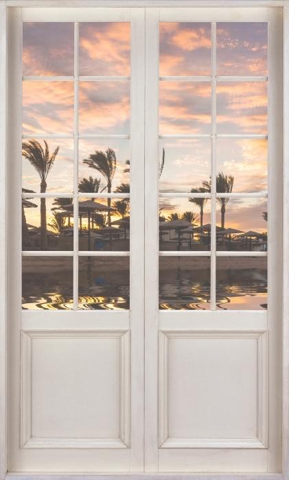 Fototapeta winylowa Białe drzwi - Zachód słońca nad piaszczystą plażą i palmami. Egipt. - Widok przez drzwi