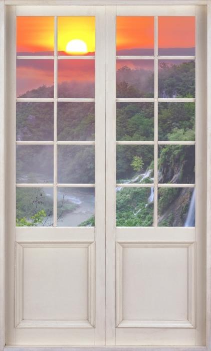 Papier peint vinyle Porte Blanche - Lever Du Soleil. Croatie. - La vue à travers la porte