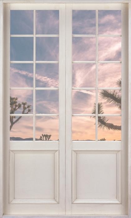 Papier peint vinyle Porte Blanche - Coucher De Soleil. Désert. Californie. - La vue à travers la porte