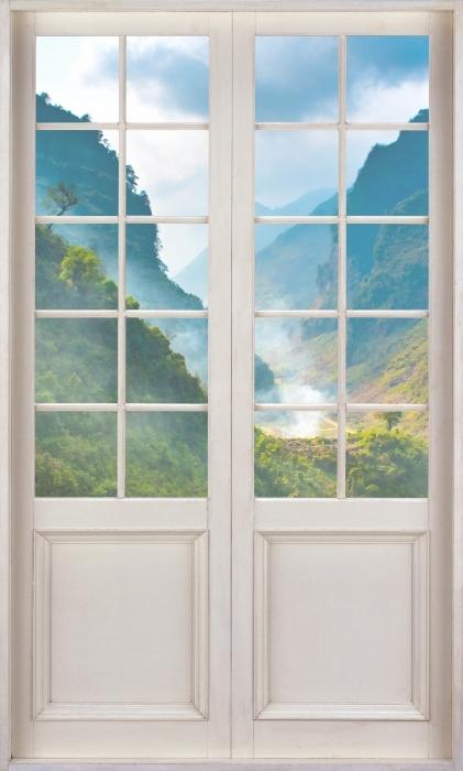 Fototapeta winylowa Białe drzwi - Ha Giang. Wietnam. - Widok przez drzwi