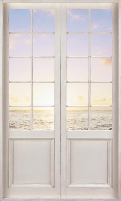 Fototapeta samoprzylepna Białe drzwi - Zachód słońca na plaży - Widok przez drzwi