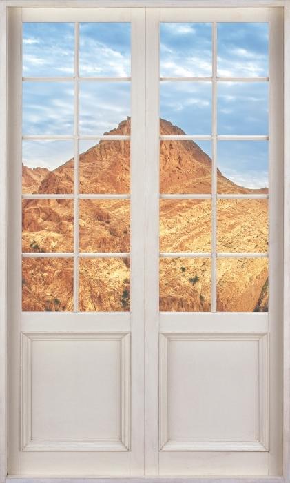 Fototapet av vinyl Hvit dør - Mountain oase - Se gjennom døren