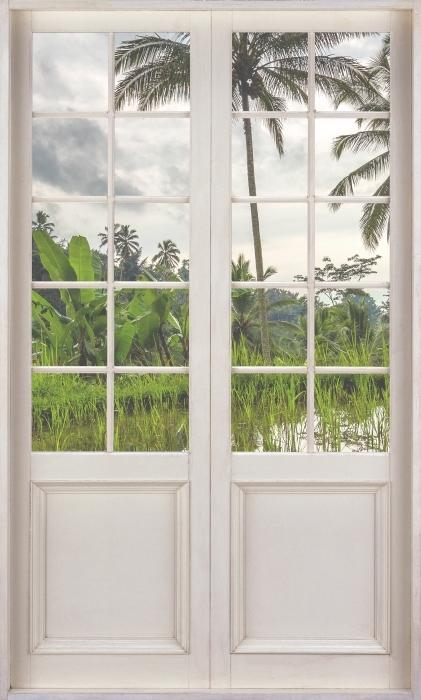 Fototapeta winylowa Białe drzwi - Palmy. Indonezja. - Widok przez drzwi