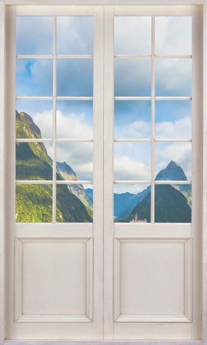 Fototapeta winylowa Białe drzwi - Wybrzeże i góry - Widok przez drzwi