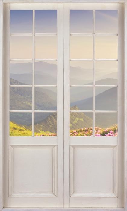 Fototapeta winylowa Białe drzwi - Górski krajobraz - Widok przez drzwi