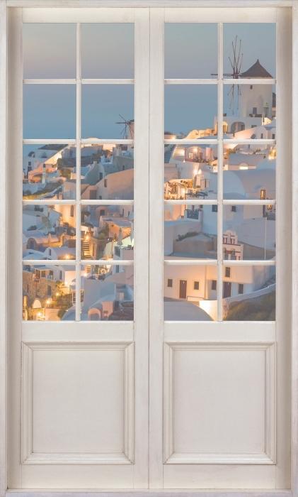 Fototapeta winylowa Białe drzwi - Piękny zachód słońca w Oia - Widok przez drzwi