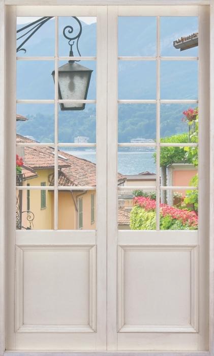 Fototapeta winylowa Białe drzwi - Malownicze miasteczko we Włoszech - Widok przez drzwi