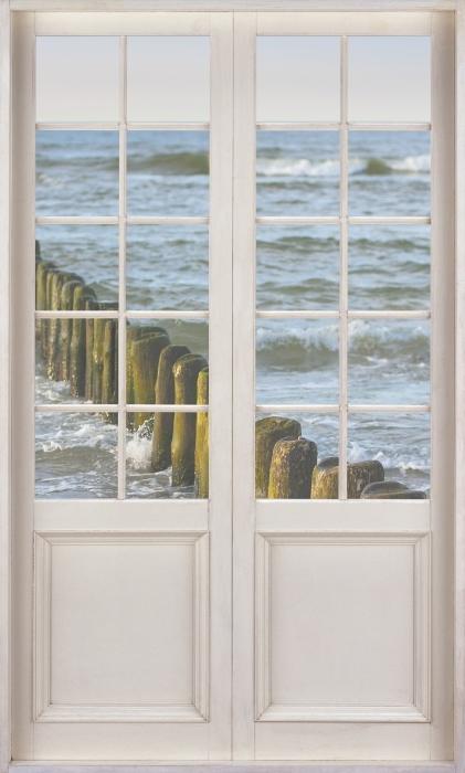 Fototapeta winylowa Białe drzwi - Zachód słońca nad Bałtykiem - Widok przez drzwi