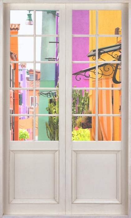 Fototapeta winylowa Białe drzwi - Kolorowa ulica w Burano. Włochy. - Widok przez drzwi