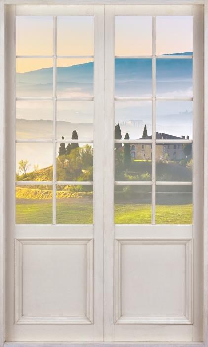 Vinyl-Fototapete Weiße Tür - Toskana in der Morgendämmerung - Blick durch die Tür
