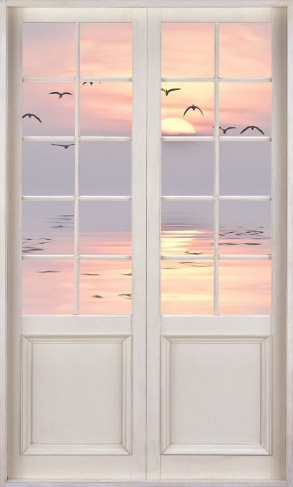 Fototapeta winylowa Białe drzwi - Zachód słońca - Widok przez drzwi
