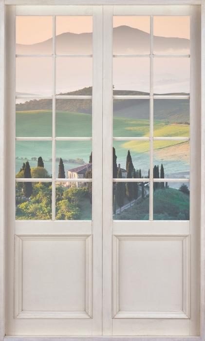 Fototapeta winylowa Białe drzwi - Toskania - Widok przez drzwi