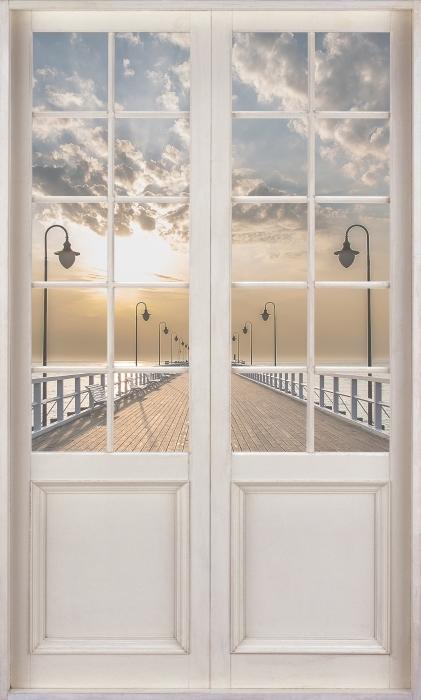 Fototapeta winylowa Białe drzwi - Wschód słońca na molo - Widok przez drzwi