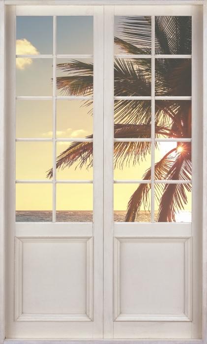 Fototapeta winylowa Białe drzwi - Palmy na tropikalnej plaży - Widok przez drzwi