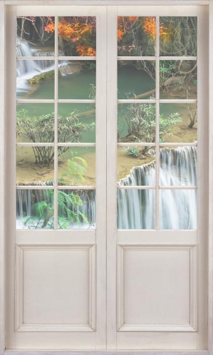 Vinyl Fotobehang White door - Waterval in het tropisch woud - Uitzicht door de deur
