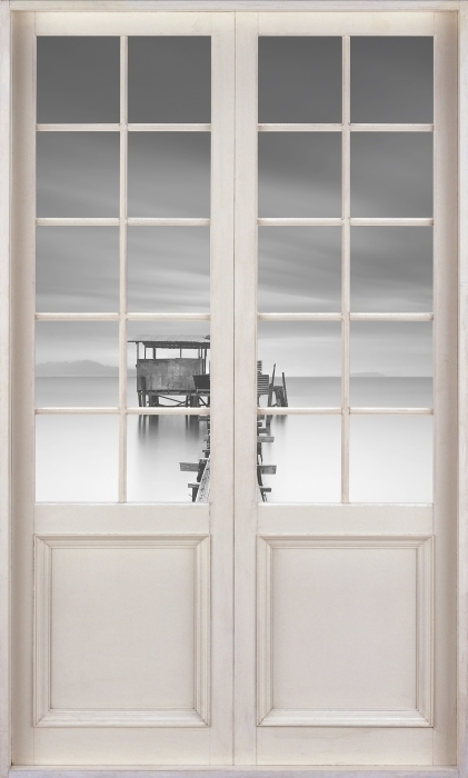 Fototapeta winylowa Białe drzwi - drewniane molo - Widok przez drzwi