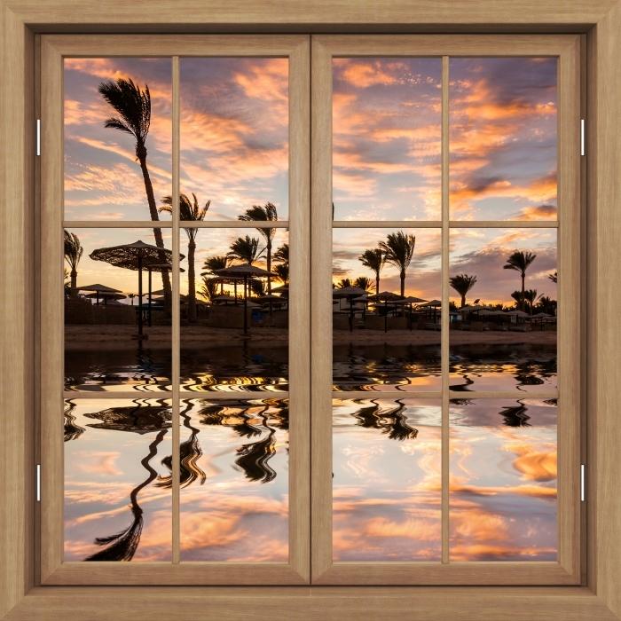 Fototapeta winylowa Okno brązowe zamknięte - Zachód słońca nad piaszczystą plażą i palmami. Egipt. - Widok przez okno