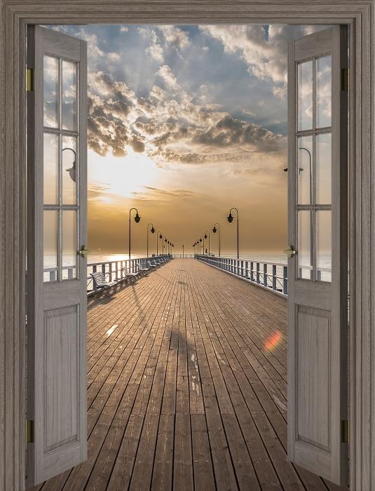 Fototapeta winylowa Brązowe drzwi - Wschód słońca na molo - Widok przez drzwi