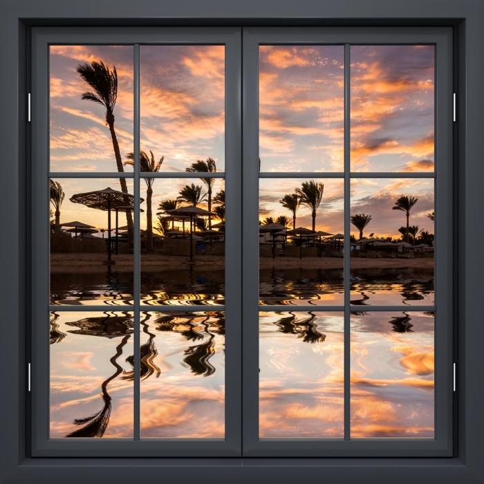 Fototapeta winylowa Okno czarne zamknięte - Zachód słońca nad piaszczystą plażą i palmami. Egipt. - Widok przez okno