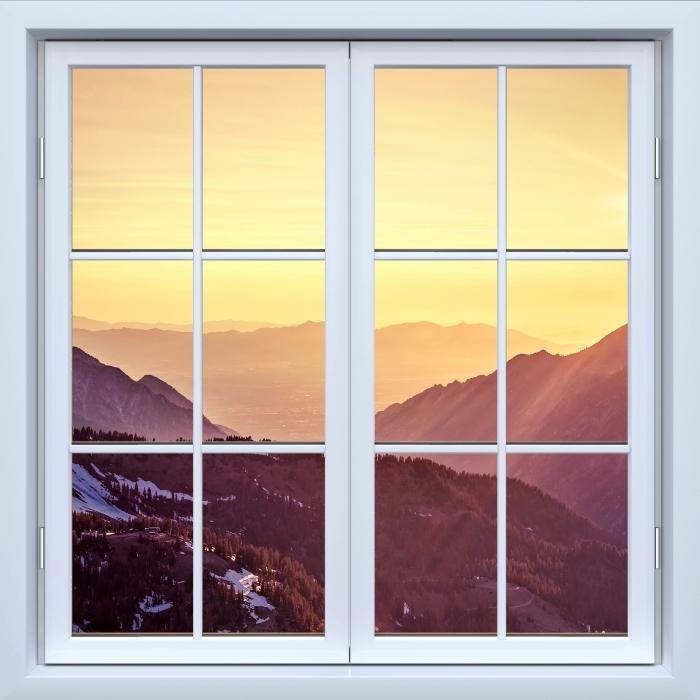 Fototapeta winylowa Okno białe zamknięte - Zachód słońca w górach - Widok przez okno
