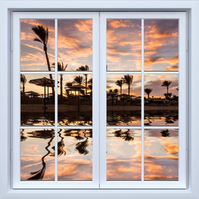 Fototapeta winylowa Okno białe zamknięte - Zachód słońca nad piaszczystą plażą i palmami. Egipt. - Widok przez okno