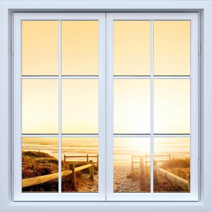 Fototapeta winylowa Okno białe zamknięte - Zachód słońca nad oceanem. - Widok przez okno