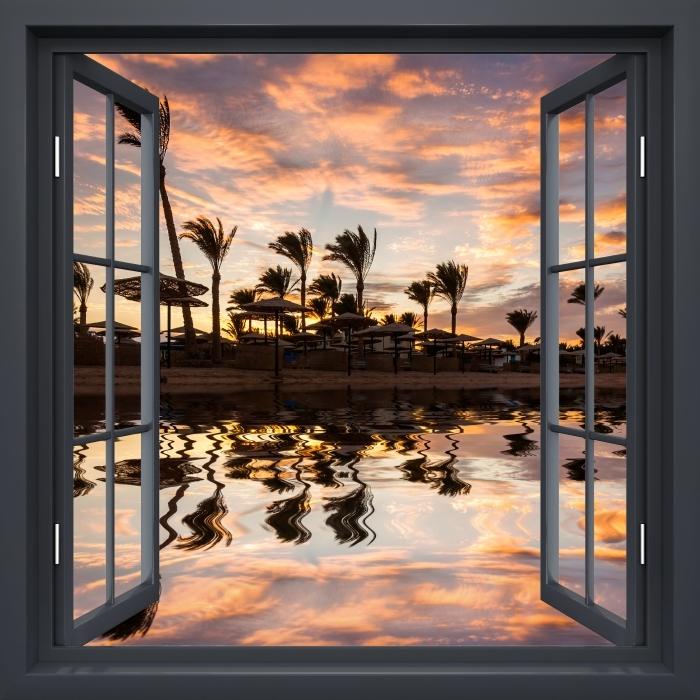 Fototapeta winylowa Okno czarne otwarte - Zachód słońca nad piaszczystą plażą i palmami. Egipt. - Widok przez okno