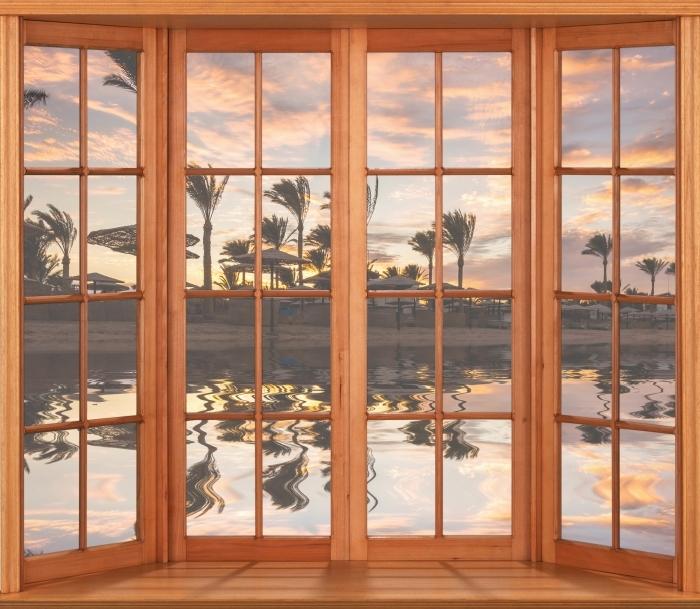 Fototapeta winylowa Taras - Zachód słońca nad piaszczystą plażą i palmami. Egipt. - Widok przez okno