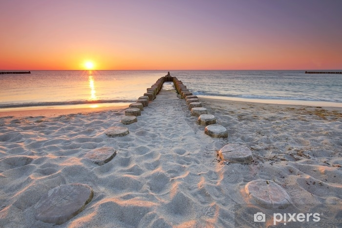 Fototapeta winylowa Lange hölzerne buhnen am strand, sonnenuntergang am meer - Krajobrazy