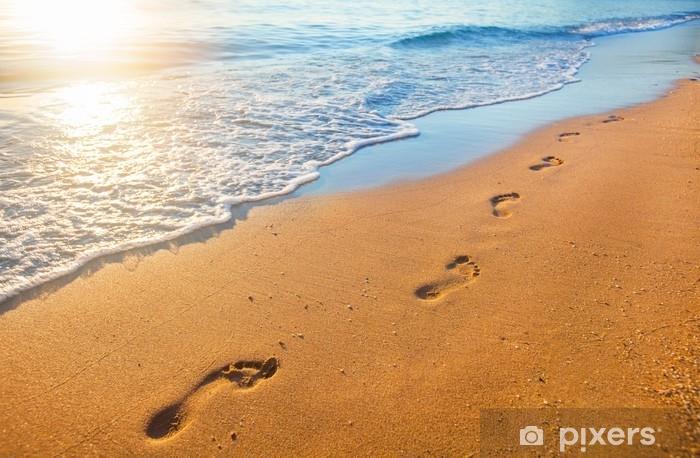 Fototapeta zmywalna Plaża, fala i ślady stóp w czasie zachodu słońca - Krajobrazy