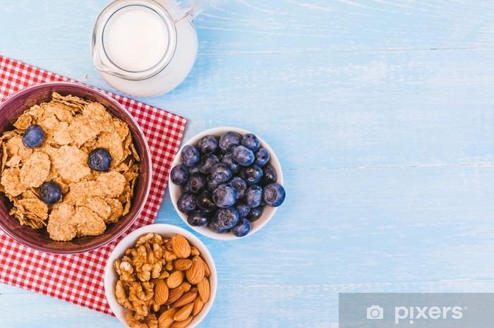 Fototapeta winylowa Zdrowe śniadanie płatki kukurydziane i mleko borówki, orzechy, migdały z miejsca na tekst makro - Jedzenie